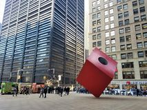 Art object Red Cube by Isamu Noguchi 1968 with people walking by. Downtown of NYC Financinal District. stock image