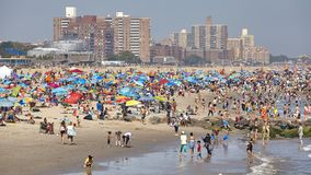 Crowded Coney Island beach on a warm, hazy day. stock photos