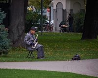 New York, USA - July, 2017: old man in a raincoat and a hat plaing saxophone in a park