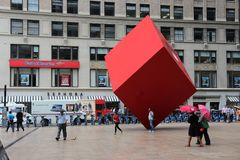 New York art. NEW YORK, USA - JULY 2, 2013: People walk under Red Cube public art in New York. The artwork by Isamu Noguchi dates back to 1968 Royalty Free Stock Image