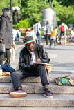 NEW YORK, USA - JUNE 3, 2018: Afro american man sitting in the park drawing. Manhattan street scene. Union square park. royalty free stock images