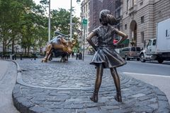 The Fearless Girl statue facing Charging Bull in Lower Manhattan, New York City. New York, USA - June 25, 2017 - The Fearless Girl statue facing Charging Bull in Stock Photography