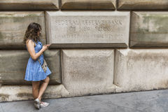 New York, USA - June 18, 2016: Federal Reserve Bank of New York sign with young woman on mobile phone Royalty Free Stock Photos