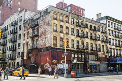 New York, USA - June 18, 2016: People walk next to old, rusty building with graffiti in Chinatown in New York City Stock Images
