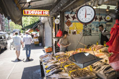 New York, USA - June 18, 2016: Seafood display and shop with vendor and customers in Chinatown in New York City with food scale Stock Image