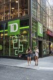 New York, USA - June 18, 2016: TD Bank branch by broadway street in NYC with two young women on smartphones Royalty Free Stock Photography