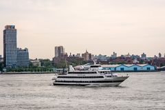 New York, USA - June 7, 2019:  Tourist boats on East River in front of Manhattan, A East River ferry boat travels the Hudson River. New York, USA - June 7, 2019 royalty free stock photos