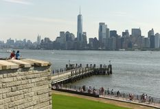 New York, USA - June 09, 2018: Tourists near the Statue of Liberty and the Lower Manhattan skyscrapers at the background. royalty free stock images