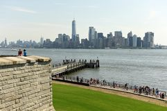 New York, USA - June 09, 2018: Tourists near the Statue of Liberty and the Lower Manhattan skyscrapers at the background. stock images