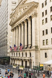 New York, USA - June 18, 2016: Vertical view of the New York Stock Exchange with American flags and people walking Stock Photo