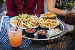 New York, USA - June 18, 2016: Waterfront cafe Pier i food, lobster roll and burger with fries, drinks and two people sitting Stock Photography