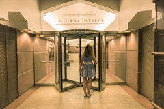 New York, USA - June 18, 2016: Young woman entering two wall street building with office of Carter Ledyard & Milburn LLP Stock Images