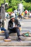 NEW YORK USA - JUNI 3, 2018: Afro- amerikanskt mansammanträde i parkerateckningen Manhattan gataplats Facklig fyrkantig Park royaltyfria bilder