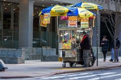 New York USA - mars 31, 2018: Man som säljer gatamat och varmt D Arkivbilder