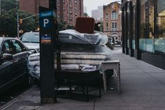Furniture and mattresses dumped outside on a street in Manhattan stock photo