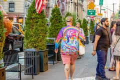 NEW YORK, USA - MAY 9, 2018: Man in colorful wearing walks by an outdoor cafe. stock photos