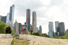 New York, USA - May 26, 2018: People in Central Park and skyscrapers of the Manhattan at the background. royalty free stock photography