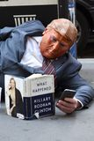 New York, USA - May 30, 2018: Street beggar wears a Trump mask a. Nd reading the book of Hillary Clinton What Happened. The man mocks the current American royalty free stock images