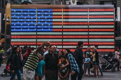 Tourists taking selfies in from on a big led American flag in Ti. NEW YORK, USA - MAY 28, 2018: Tourists taking selfies in from on a big led American flag in stock photos