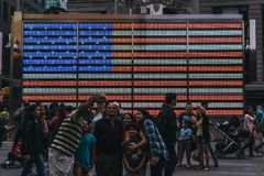 Tourists taking selfies in from on a big led American flag in Ti stock images