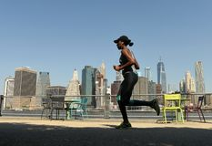 New York, USA - May 25, 2018: A woman the run in Brooklyn Bridge. Park with financial district in lower Manhattan at the background stock photography