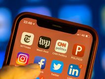 News agency app icons on new smartphone. NEW YORK, USA - NOVEMBER 7, 2017: News agency app icons on new smartphone display close-up around other social media royalty free stock photo