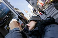 Cellular Photography Tourist Times Square Manhattan New-York Win. New-York, USA - November 6th, 2012: An adult Caucasian woman in her 30's using her smartphone stock photos