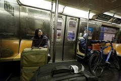 Woman with Suitcase and Cycler in New-York Subway. New-York, USA - November 8th, 2012: An adult woman with luggage and an adult man with bicycle sitting in the Stock Photo