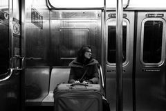 Woman with Suitcase in New-York Subway. New-York, USA - November 8th, 2012: An adult woman with luggage sitting in the Brookly bound (downtown) A train subway in Royalty Free Stock Photos