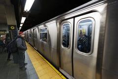 Commuters and Subway 42nd Street  Station Manhattan New-York. New-York, USA - November 6th, 2012: Several commuters are standing on the 42nd street subway Stock Photo