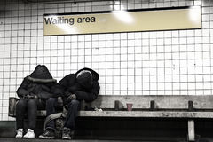 Two People Sleeping in NYC Subway Waiting Area Stock Images