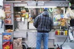 NEW YORK, USA - 24 NOVEMBRE : Support de nourriture de coin de la rue avec le vendeur Images stock