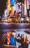 Times Square, New York City. NEW YORK, USA - OCT, 2017: A puddle reflects the nighttime lights of Times square in Manhattan. COPY SPACE AVAILABLE stock photo