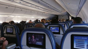 New York, USA - OKTOBER 12, 2016: Air Travel. The passengers inside the aircraft cabin, watching videos and movies on. Air Travel. The passengers inside the stock footage