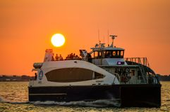 New York, New York, USA 08 20 2017 Relaxing people on ferry to Wall Street from Rockaway with orange dusk behind royalty free stock image