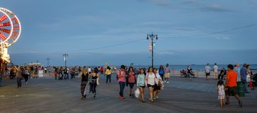 Coney Island Beach in NYC. NEW YORK, USA - Sep 23, 2017: Coney Island Beach in NYC. Vacationers walking on the shore in evening time. Coney Island is well known royalty free stock image