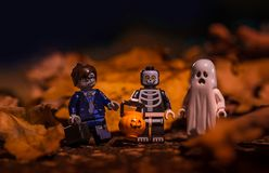 Lego Halloween trick and treat. New York, USA - September 28, 2017 - Lego Halloween trick and treat Zombie, Skeleton and Ghost with leaves in background royalty free stock photos