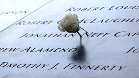 Names and a rose at the 9/11 Memorials. NEW YORK, USA - September 29, 2017: Names of the victims and a white rose at the National September 11 Memorial, in New Stock Photos