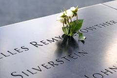 Names and a rose at the 9/11 Memorials. NEW YORK, USA - September 29, 2017: Names of the victims and a white roses at the National September 11 Memorial, in New Stock Images