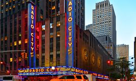 New York USA, urban classic building, colors and neon lights of Radio City Music Hall in Manhattan with urban traffic stock photography