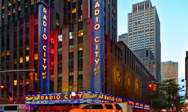 New York USA, urban classic building, colors and neon lights of Radio City Music Hall in Manhattan with urban traffic and yellow t royalty free stock photo
