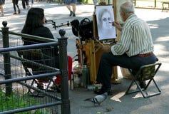 NEW YORK, VEREINIGTE STAATEN - 25. AUGUST 2016: Ein Künstler skizziert eine Frau im Central Park an einem Sommertag Lizenzfreie Stockfotos