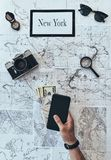 New York is waiting!. Close up top view of man holding smart phone, passport and money with sunglasses, photo camera, compass, magnifying glass lying on map royalty free stock photos