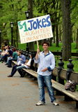 New York: Young Man in Central Park. A smiling young man on the Mall in Central Park holds up a sign offering to tell passerby jokes for $1.00 each in New York Royalty Free Stock Image