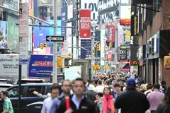 Tourists and consumerism in New York City. New Yorkers and tourists make their way amongst various signage in New York on 5/19/17 Royalty Free Stock Photography