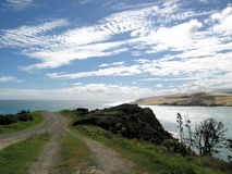 New Zealand. Dirt Road on New Zealand with Water, Blue Sky Stock Photography