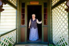 Retired elderly english woman stands outside her door royalty free stock images