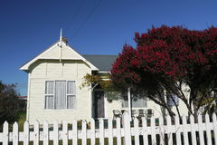 New Zealand: classic wooden home. Classic 19th century wooden home with native red manuka tree and white picket fence in Waipu Northland New Zealand stock photography