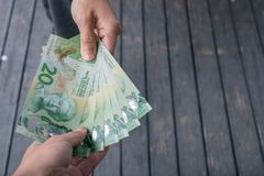 Cropped shot view of someone giving the money New Zealand 20$ dollars to other person. New Zealand dollar is the official currency of New Zealand since 1967 royalty free stock images