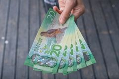 Cropped shot view of someone showing the money New Zealand 20$ dollars. New Zealand dollar is the official currency of New Zealand since 1967 stock image